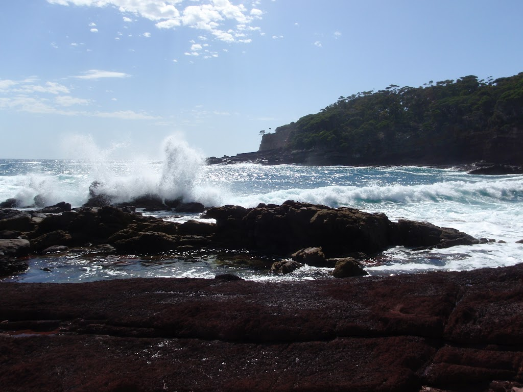 Waves crashing into red sands bay