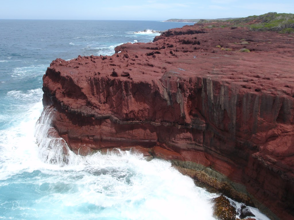 Red cliffs with waves crshing