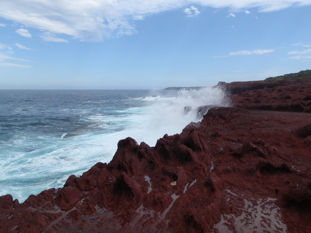 Waves crashing onto red cliffs