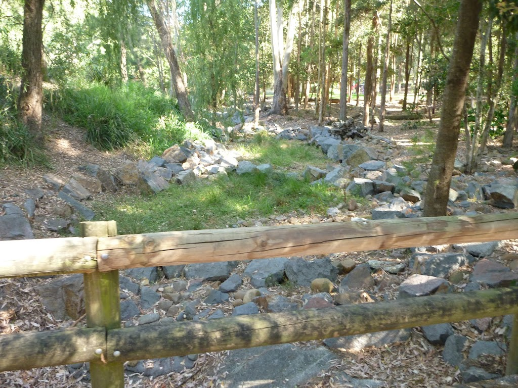 Dry rocky creek bed with timber barrier in Carnley Ave Reserve