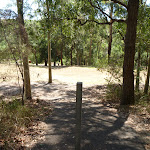 Metal post in footpath with a large grassy clearing in Richley Reserve